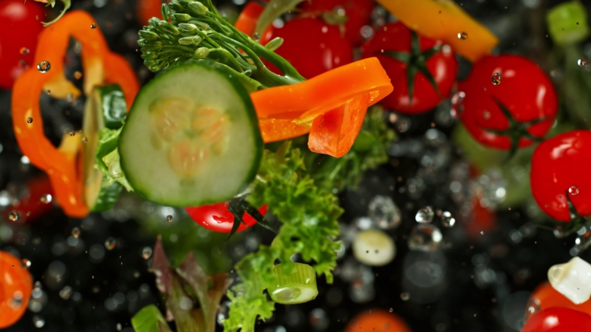 Super Slow Motion Shot of Flying Cuts of Colorful Vegetables and Water Drops on Black background at 1000fps. | Shutterstock HD Video #1042139056