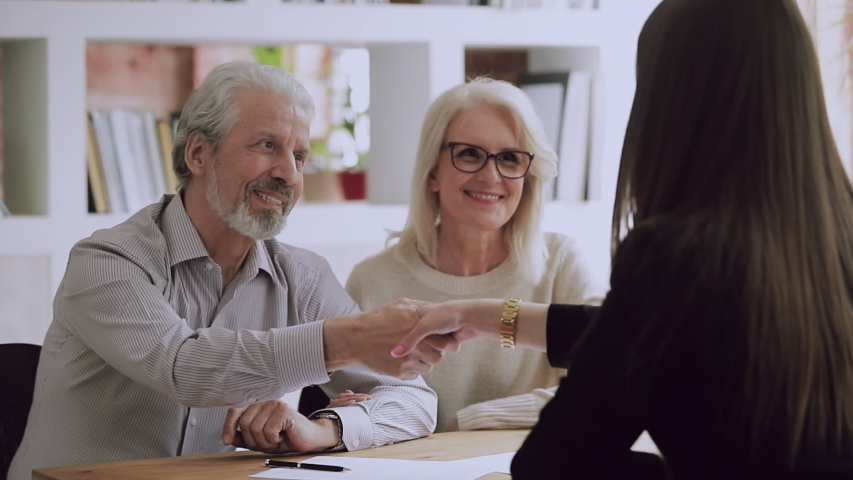 Happy middle aged family couple meeting female real estate agent, financial advisor or lawyer, discussing contract details, making agreement at office. Satisfied client shaking hands with saleswoman.