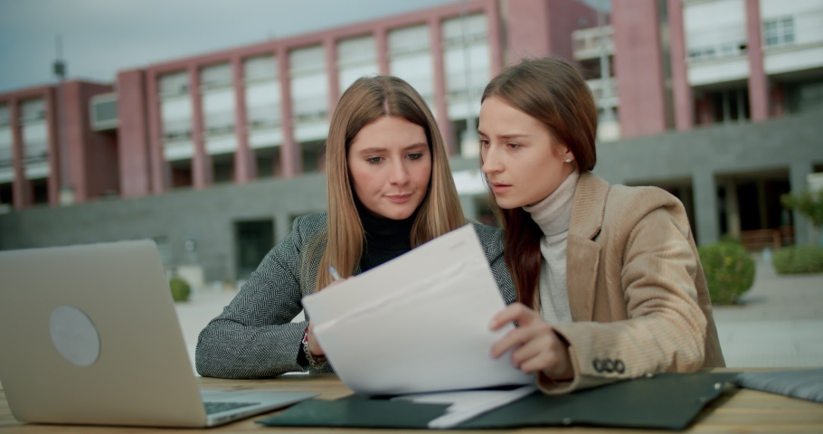 Brainstorming moment of two beautiful business students making research project outdoor, teamwork of females working on homework looking at papers and using silver laptop at outdoor workplace Royalty-Free Stock Footage #1042151962