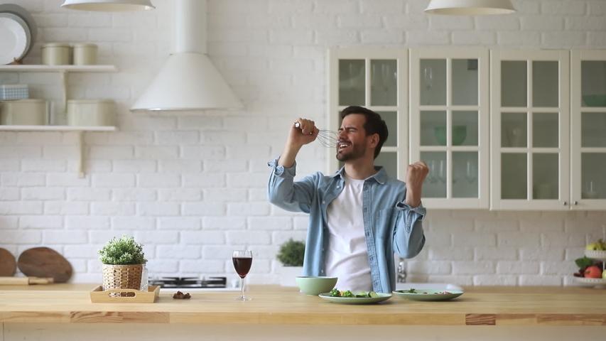 Overjoyed young man in eyeglasses using whisk as microphone, singing, dancing, enjoying favorite music during food preparation at home. Happy guy having fun while cooking breakfast in kitchen.
