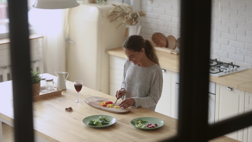 Top view young smiling mixed race woman standing at countertop, chopping vegetables in modern kitchen. Positive millennial lady preparing food alone at home, dreaming about romantic evening. | Shutterstock HD Video #1042155751