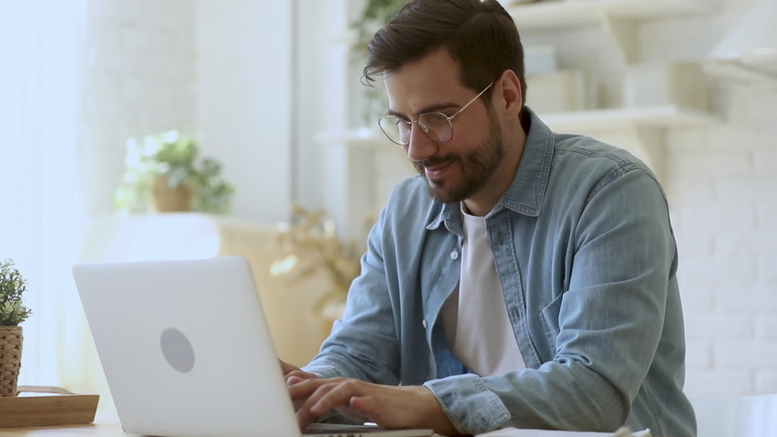 Concentrated young man freelancer in eyeglasses looking at laptop screen, working remotely at home. Head shot focused smiling guy chatting in social network, typing message, internet web surfing. | Shutterstock HD Video #1042155763