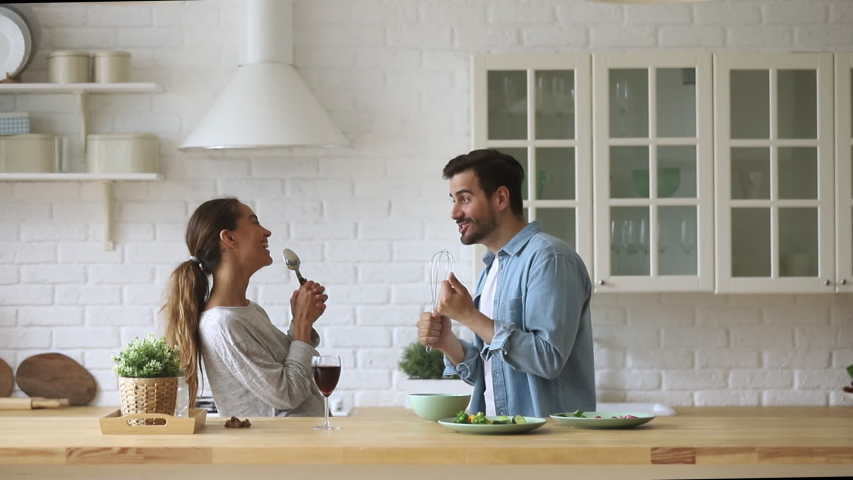 Overjoyed young married spouse using different kitchenware as microphones, pretending to be singers. Excited happy mixed race family couple dancing to favorite music, singing song as duo in kitchen. | Shutterstock HD Video #1042155847