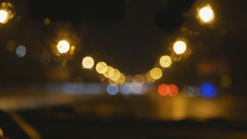 Night city through the wet window of a moving car with a wiper.Rainy dark night view of the movement of the wipers from the passenger compartment. Night city through the car window | Shutterstock HD Video #1042163833