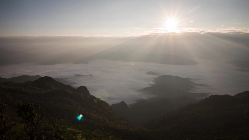 Timelapse. Sun rising over mountains with fog and the light shines beautifully. A tourist destination on a hilltop during the foggy and beautiful light in the morning and sunset in Chiang Rai Thailand | Shutterstock HD Video #1042165837
