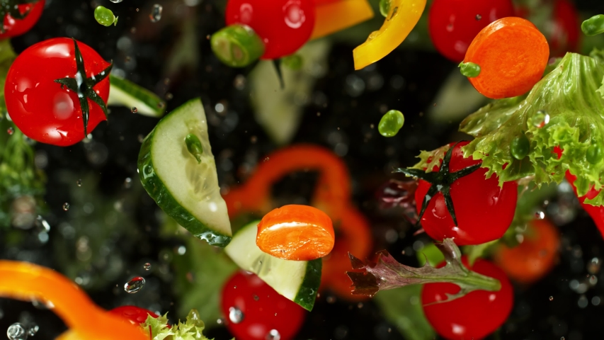 Super Slow Motion Shot of Flying Cuts of Colorful Vegetables and Water Drops on Black background at 1000fps.