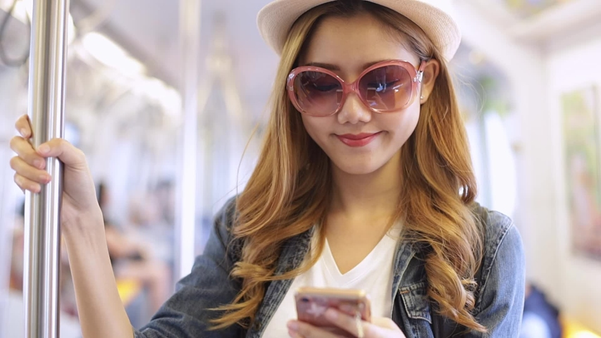 Portrait of attractive smiling Asian  girl in train using smartphone chatting with friends woman hand internet technology cellphone city .