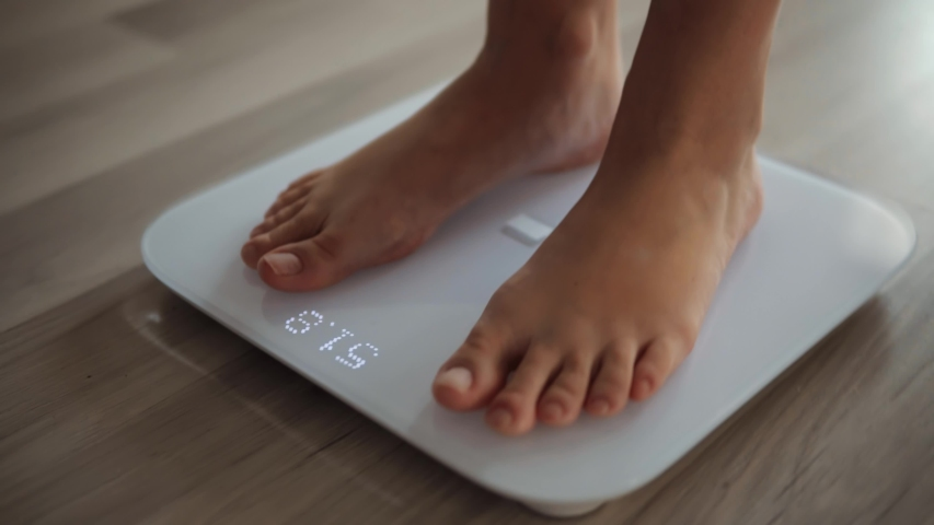 Female On Scales Measure Weight.Girl Legs Step On Bathroom Scale.Diet Woman Feet Standing Weighing Scales On Room.Close Up Woman Checking BMI Weight Loss.Human Barefoot Measuring Body Fat Overweight. Royalty-Free Stock Footage #1042177819