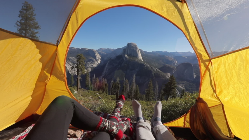 Two pairs of legs in the opening of the tent, against the backdrop of the mountain landscape of Sierra Nevada and the cliff of Half Dome.The sun illuminates the tent.Outside landscape looks inspiring.   Shutterstock HD Video #1042183936