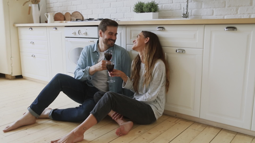 Full length happy young married couple sitting on warm heated floor. clinking glasses with wine, celebrating new house purchase, successful mortgage investment. Laughing family spouse enjoying dating. | Shutterstock HD Video #1042185604