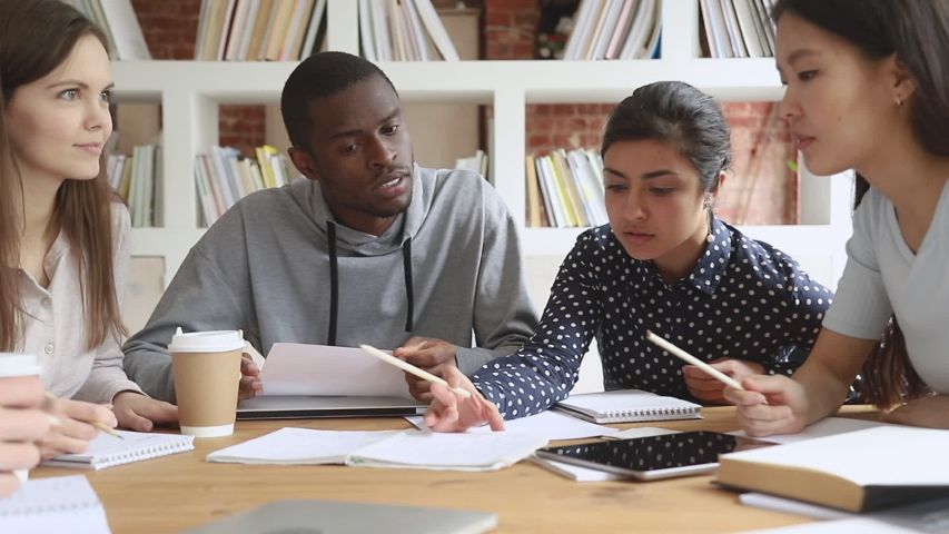 Focused indian student pointing at paper notes, preparing for college examinations with multiracial groupmates. Concentrated mixed race friends working on research project together in library. Royalty-Free Stock Footage #1042185622