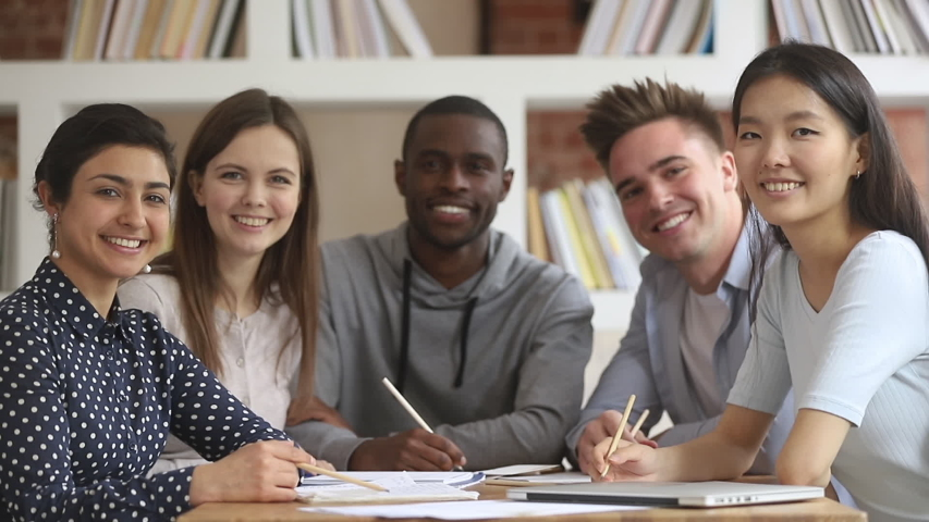 Pleasant smiling mixed race students sitting at table in library, looking at camera. Group of multiracial young people posing for photo in classroom or office. Smart undergraduates studying together. Royalty-Free Stock Footage #1042185712
