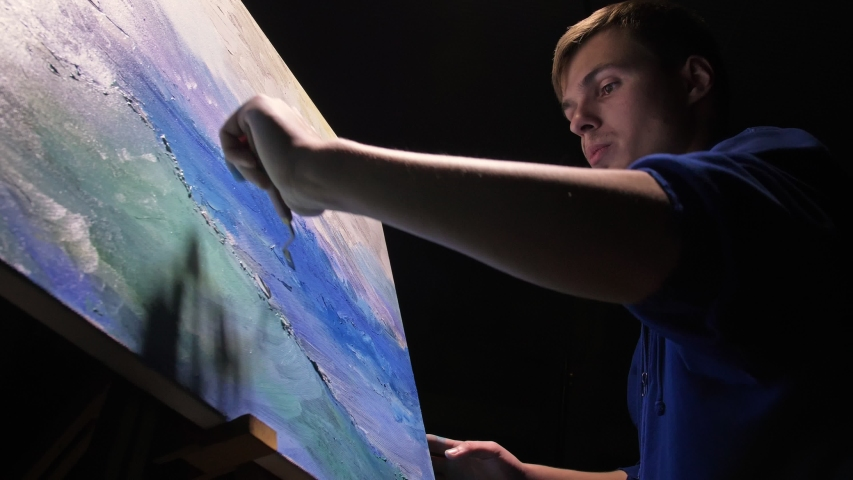 Artist copyist paint seascape with ship in ocean. Craftsman decorator draw as boat sail on blue sea with acrylic oil color. Draw finger, brush, knife palette. Indoor. Dark magic cinematic look. #1042192351
