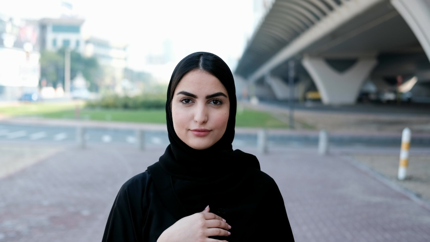 Walking Arab woman on Abaya. Beautiful Young Arabic girl on Hijab moving forward as she walks at the street with blurred moving cars as background in UAE