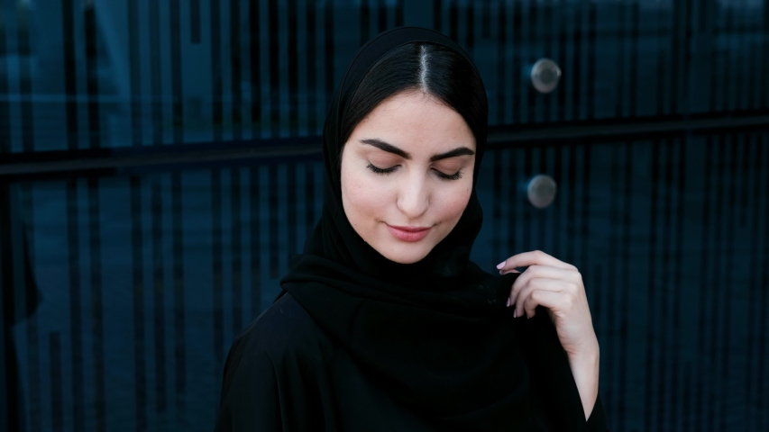 Emirati Arab girl looks at the camera on Abaya.  Arabic business woman on Hijab stares at the front. Close up follow focus of Middle Eastern UAE female national