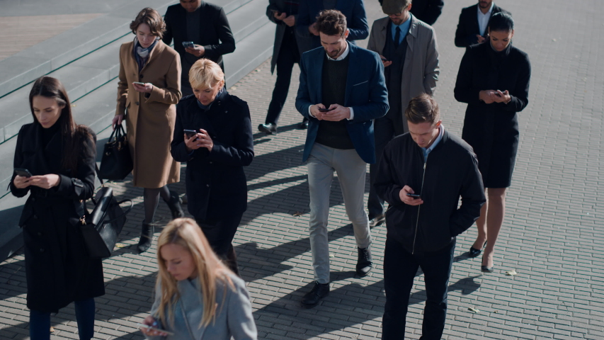 Multicultural Diverse Office Managers and Business People Commute to Work in the Morning or from Office on a Sunny Day on Foot. Pedestrians are Dressed Smartly. Successful People Holding Smartphones.