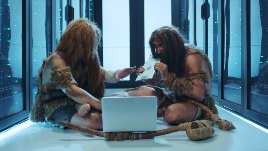 Primitive first humans traveling through time working on laptop at server room. Ancient IT administrators diagnosing server cabinet with notebook staying in futuristic dataccenter. | Shutterstock HD Video #1042212982