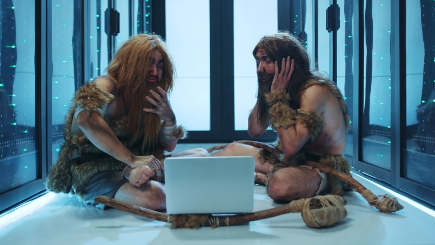 Tribe of prehistoric wild people sitting inside server cabinet, discovering modern technology, using a laptop computer. Funny cavemen in data center. Human evolution. | Shutterstock HD Video #1042212991
