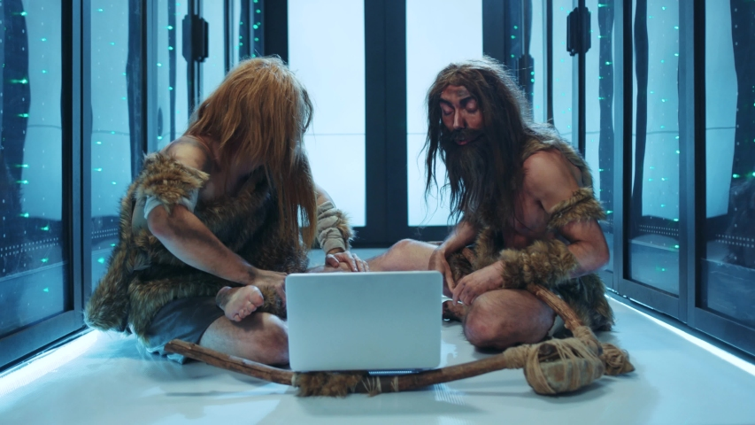 Primeval wild men of hunter-gatherers discovering technology inside futuristic data center. Prehistoric savages IT engineers using a laptop for maintenance in server cabinet. | Shutterstock HD Video #1042213000