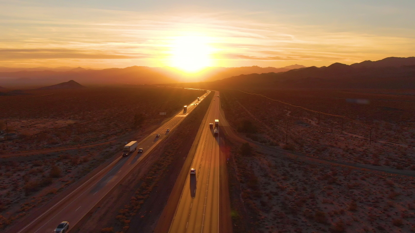 AERIAL, LENS FLARE: Scenic shot of 18 wheeler trucks and cars crossing Mojave desert at dusk. Golden evening sun rays shine on the traffic moving up and down the straight freeway in rural California.