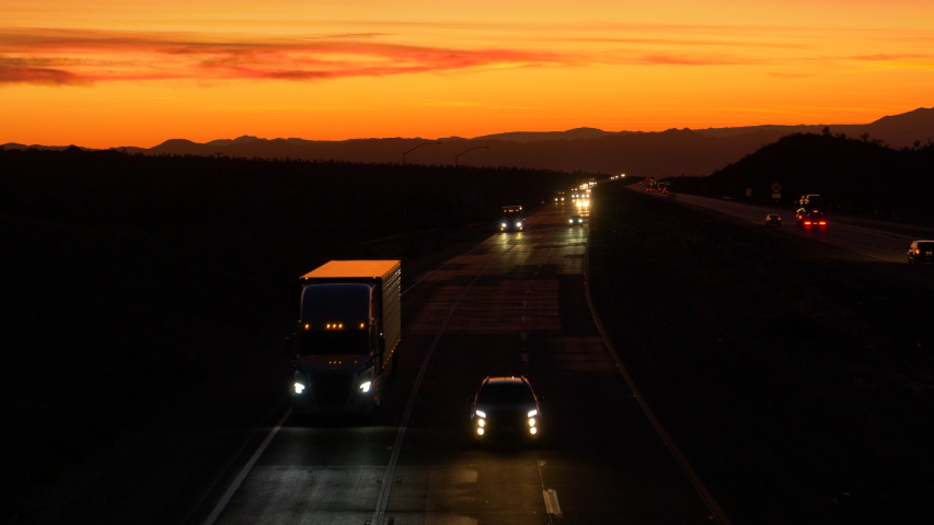 DRONE: Scenic shot of evening traffic driving along the highway leading across the Mojave desert at twilight. Commuters and truck drivers cross the Mojave desert on a picturesque summer evening.   Shutterstock HD Video #1042216339