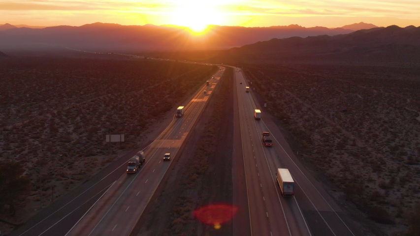 AERIAL, SUN FLARE: Cars and trucks cross the Mojave desert on a sunny summer morning. Big rig trucks and cars drive along the scenic highway running across the barren California landscape at sunset.