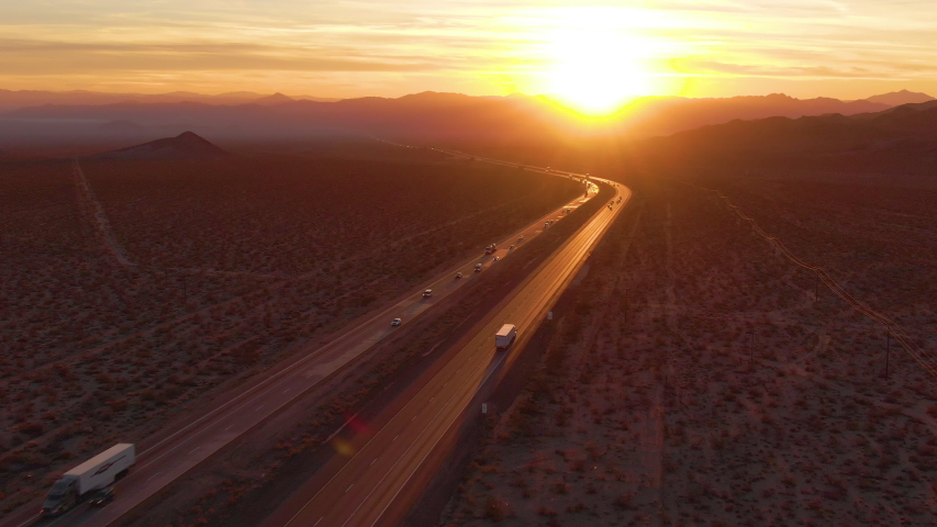 DRONE, LENS FLARE: Flying behind a freight truck driving along the Mojave freeway at sunrise. Freight trucks and cars move along the asphalt highway running across rural California on a sunny morning. | Shutterstock HD Video #1042216369