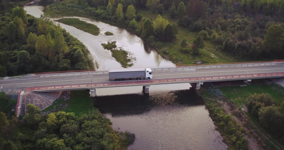 One White Truck with trailer driving on bridge through mountain river / Freeway traffic at summer sunset in hilly landscapes - Aerial drone view