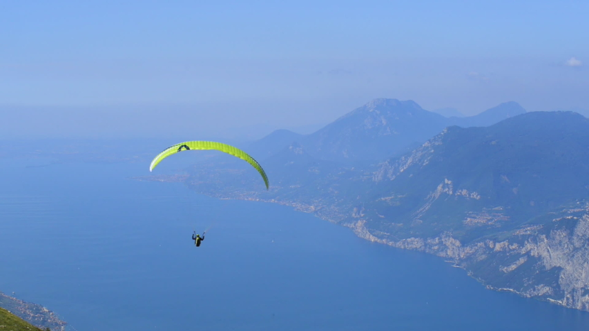 Paraglider flying over the Garda Lake (Lago di Garda or Lago Benaco), Panorama of the gorgeous Garda lake surrounded by mountains. Paragliding is very popular sport in Monte Baldo. Malcesine, Italy | Shutterstock HD Video #1042223773