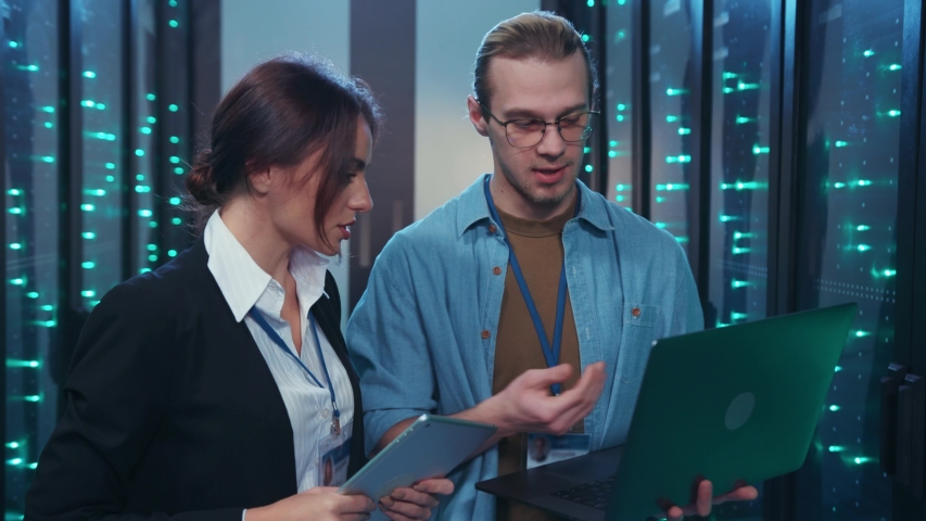 IT head woman administrator coworking with young server assistant showing neural network project on laptop talking about work in server room of data center. #1042229071