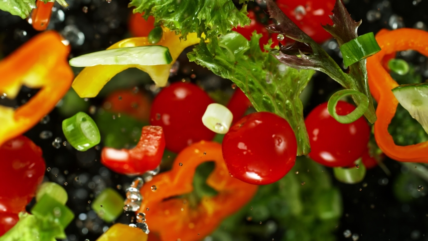 Super Slow Motion Shot of Flying Cuts of Colorful Vegetables and Water Drops on Black background at 1000fps. | Shutterstock HD Video #1042233439