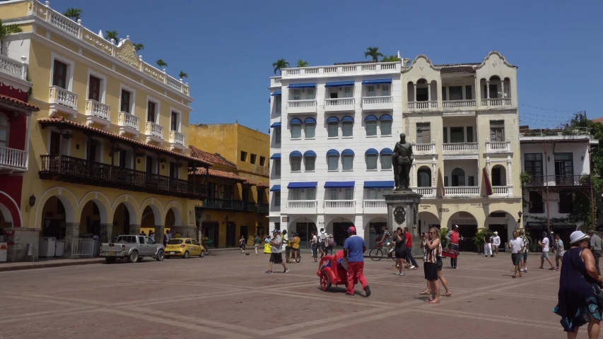 Cartagena, Colombia - November 15th 2019: Tourist walking on Plaza de los Coches with the statue of Pedro de Heredia | Shutterstock HD Video #1042233694