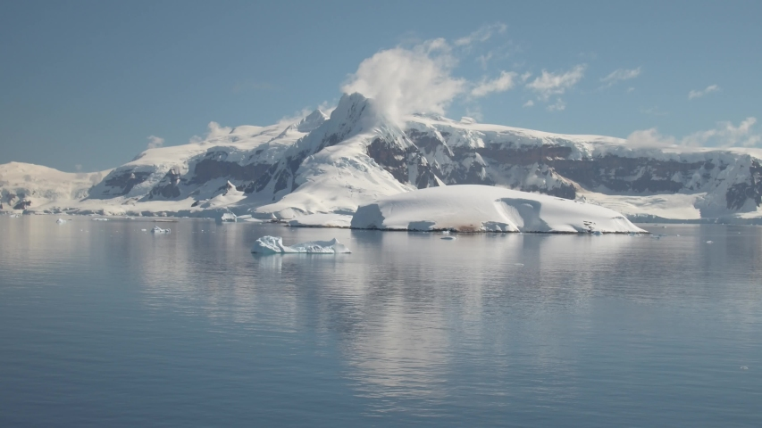 The glacial terrain of Antartica with snowy reflections in the waters and brilliant blue skies