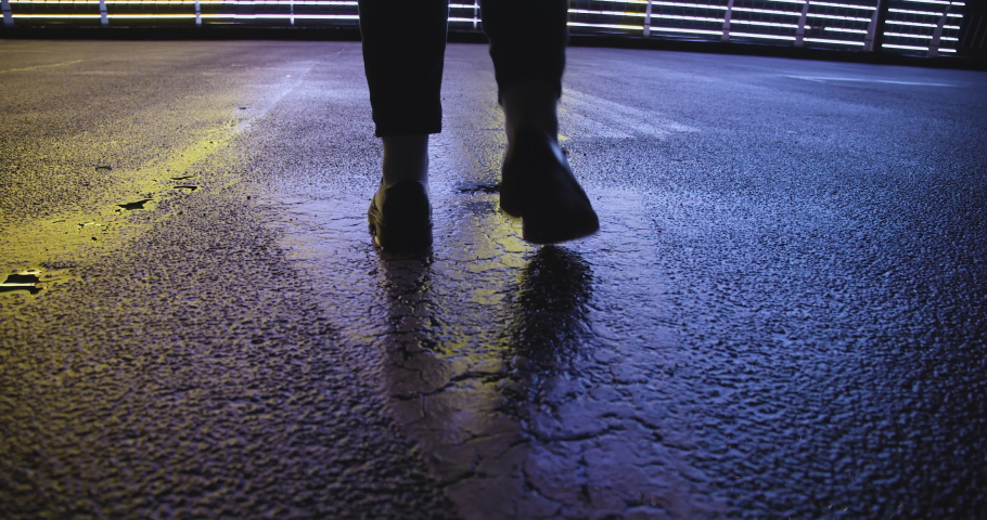 Feet of young person wearing leather shoes walking big city street after rain