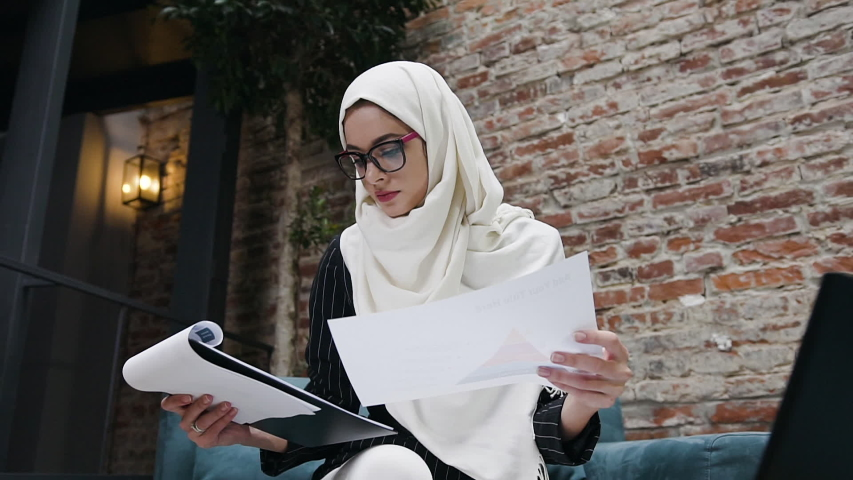 Front view of pretty serious muslim business lady with glasses in white hijab which sitting on comfortable office couch and working with financial documents and laptop Royalty-Free Stock Footage #1042242139