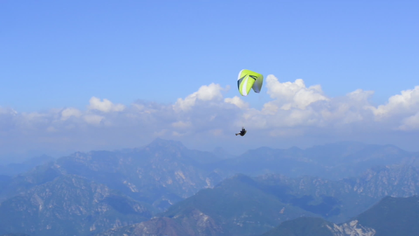 Paraglider flying over the Garda Lake (Lago di Garda or Lago Benaco), Panorama of the gorgeous Garda lake surrounded by mountains. Paragliding is very popular sport in Monte Baldo. Malcesine, Italy | Shutterstock HD Video #1042242346