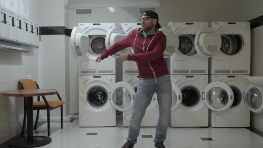 Man Dancing Viral Dance And Have Fun In the Laundry Room. Happy Guy Enjoying Dance, Having Fun Together, Party. Joyful Man With beard in Cap and Glasses Dancing Cheerful In Laundry Room. Slow Motion. | Shutterstock HD Video #1042244641