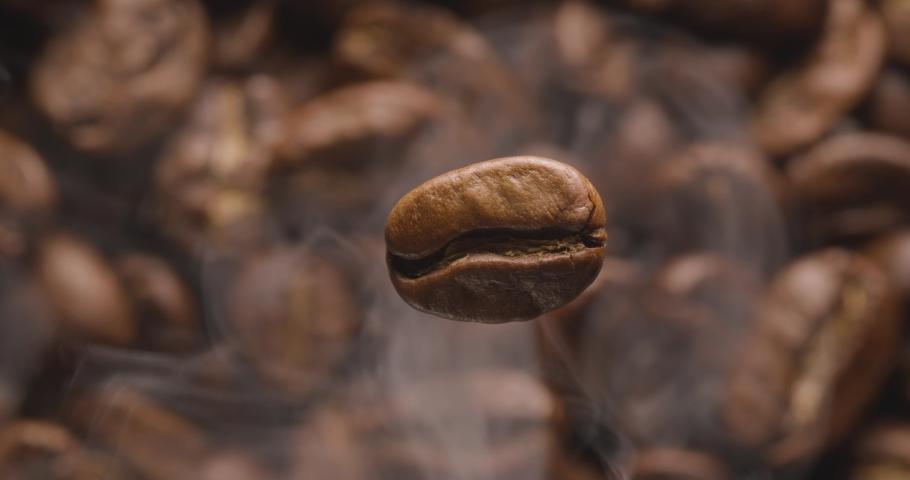 Coffee bean macro rotates, below - the background of roasting coffee beans with smoke. Blackmagic 6K camera. | Shutterstock HD Video #1042246957