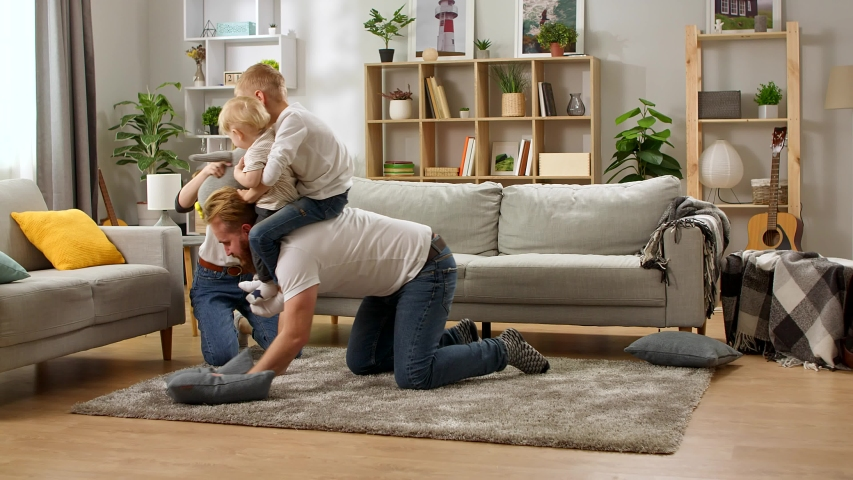 Young dad crawling on floor carrying cute small child sons on back