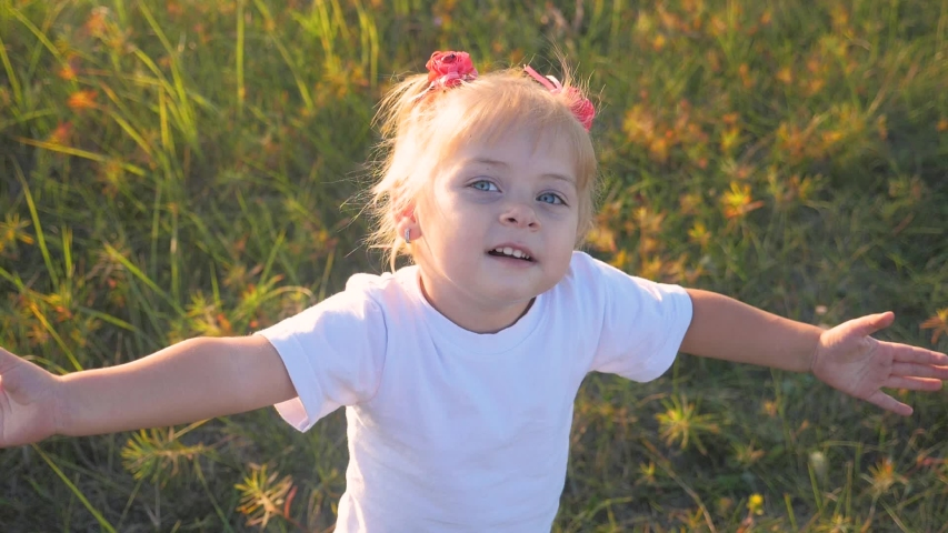 small little girl child hands drawn to heaven concept happy family religion. little daughter closed his eyes spread his arms to the sides on the nature in the park at sunset slow motion video #1042265272