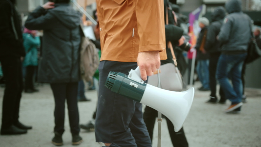 Man walk and hold megaphone in hand and shouting closeup. Human rights. Crowd people day demonstration. Rebel go shout loudspeaker strike protest close up. Revolution in city street. Political rally.