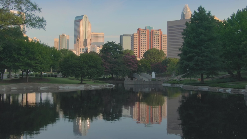 Aerial: flying over pond & fountain in Marshall Park in downtown Charlotte. North Carolina, USA.