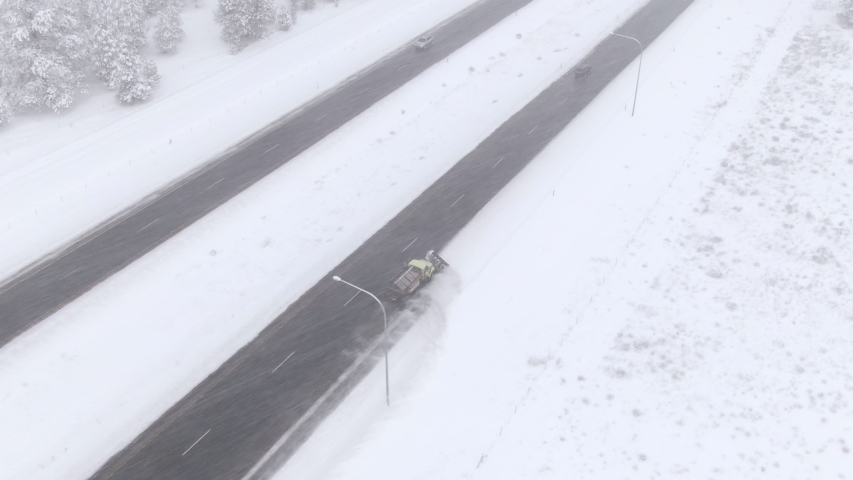 DRONE: Flying above a wintry evergreen forest as snowplow clears the icy highway in Washington, USA. Truck ploughs fresh snow gathered on the side of an asphalt freeway. Truck cleaning the icy road.