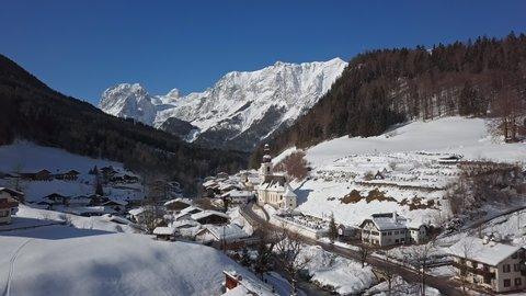 Winter flight over Ramsau town and famous Parish church St. Sebastian, Berchtesgaden, Bavarian Alps, Germany