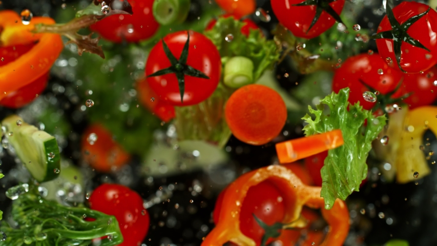 Super Slow Motion Shot of Flying Cuts of Colorful Vegetables and Water Drops on Black background at 1000fps. | Shutterstock HD Video #1042295455