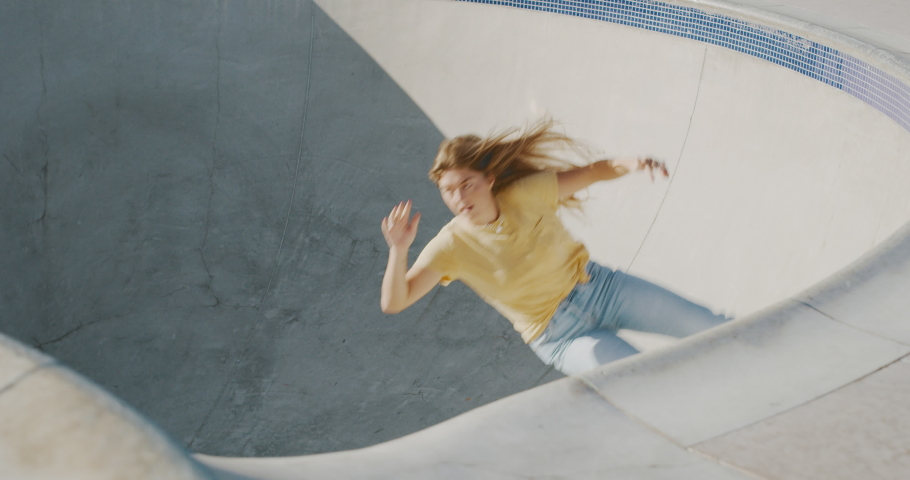 Girls in extreme sports, stylish retro skater girl does a surf style carving turn on her skateboard in a concrete skate pool bowl | Shutterstock HD Video #1042297486