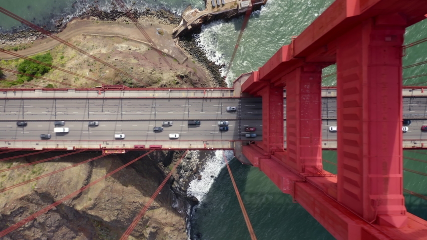 Many vehicles drive along the Golden Gate Bridge road. Bridge roadbed goes from above the water and to the land. Aerial topdown footage. Famous tourist attraction of San Francisco, California. 4k