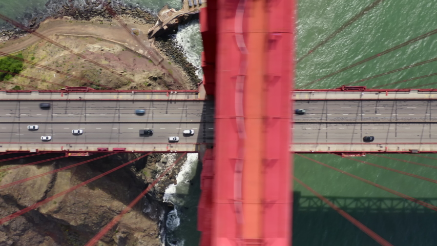 Golden Gate Bridge. Aerial top view over the famous road bridge. Beautiful suspension construction crosses the land and the water. Vehicles drive along the bridge. San Francisco, California. 4k