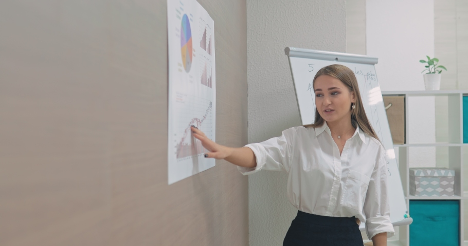 Happy young woman businessman explains to colleagues about the financial income of the corporation, shows the graphs. Portrait view. #1042304947