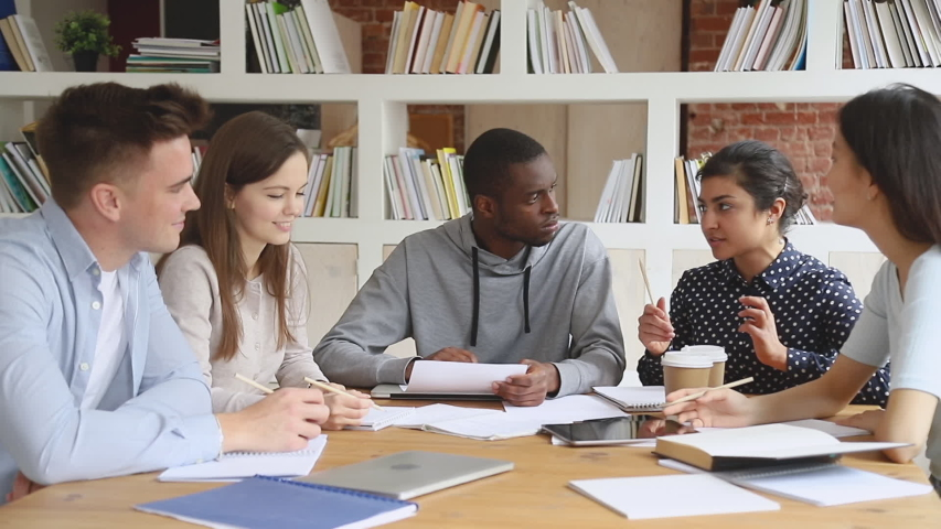 Concentrated mixed race students listening to smart indian female groupmate, explaining educational material. Focused international university friends preparing to college exams together in library. Royalty-Free Stock Footage #1042308985